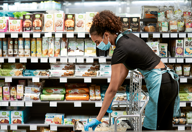 Grocery store employee stocking natural, organic, specialty, and fresh grocery products on the shelf